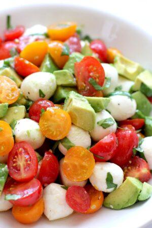 Close up of tomato mozzarella avocado salad in a white bowl.