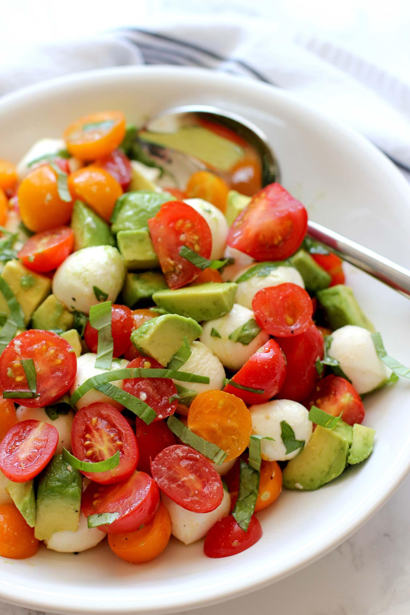 Tomato mozzarella avocado salad in a white bowl with a silver spoon.
