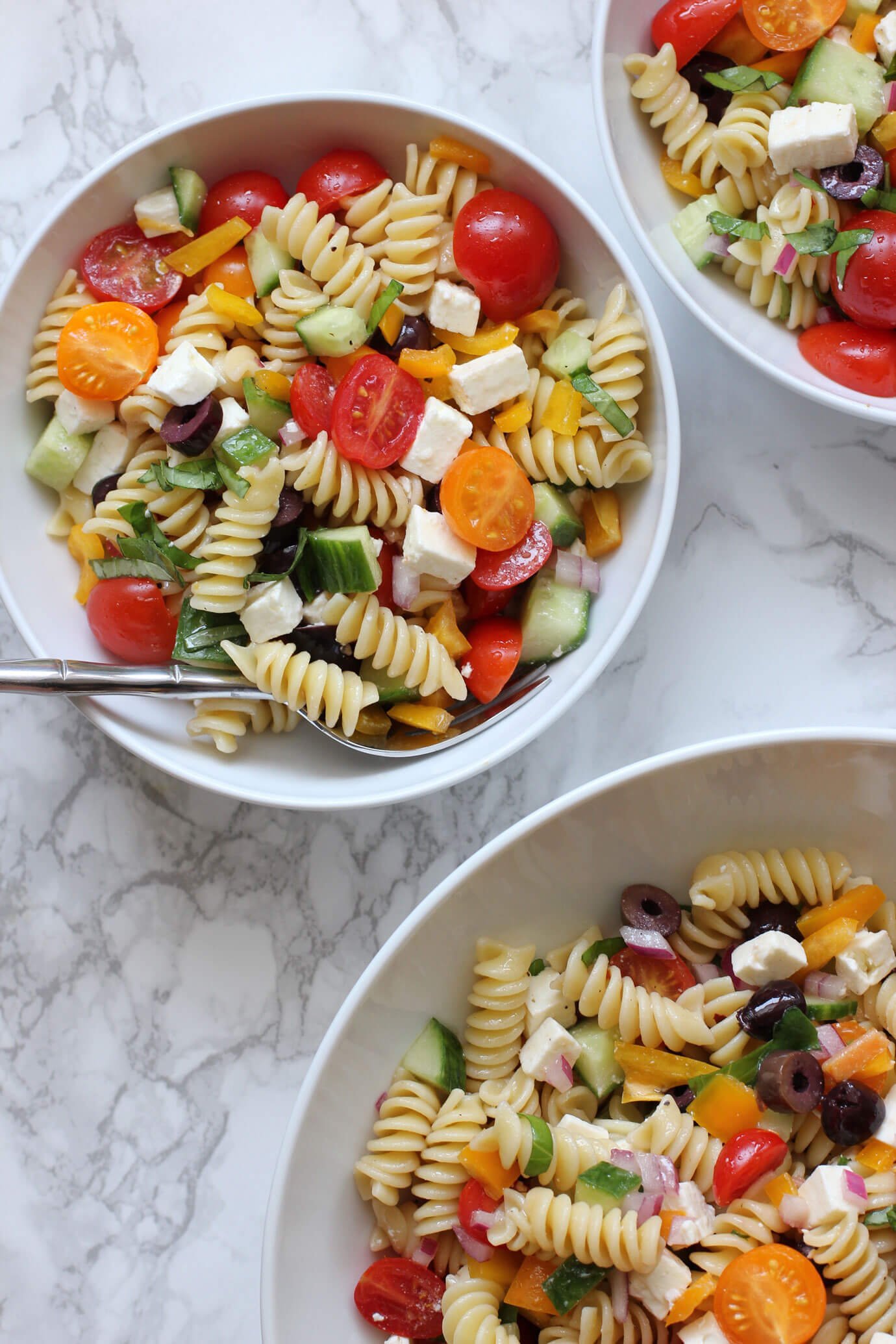 Greek pasta salad in a white bowl with a fork next to additional bowls of greek pasta salad.