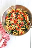 Pasta with sautéed cherry tomatoes and spinach