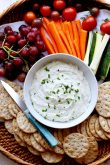 Wicker tray with bowl of whipped goat cheese, crackers, grapes and veggies and a blue handled knife.